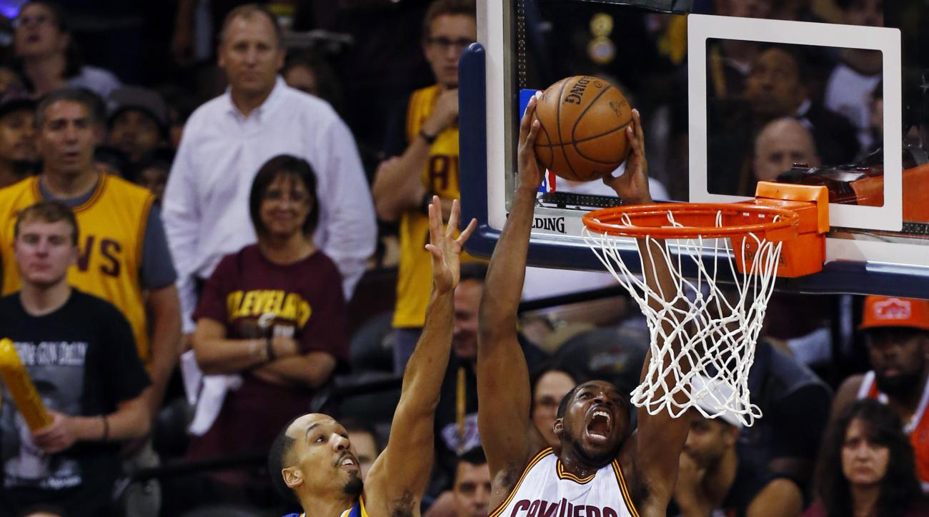 Cleveland Cavaliers center Tristan Thompson (13) dunks against Golden State Warriors guard Shaun Livingston (34) during the first half of Game 6 of basketball's NBA Finals in Cleveland, Tuesday, June 16, 2015. (AP Photo/Paul Sancya)