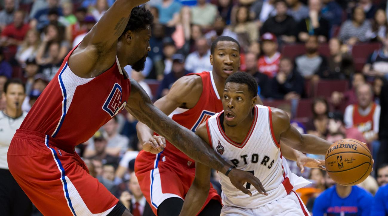 Toronto Raptors' Kyle Lowry, right, drives to the basket against Los Angeles Clippers' DeAndre Jordan, left, as Wesley Johnson, back, watches during the second half of an NBA preseason basketball game, Sunday, Oct. 4, 2015 in Vancouver, British Columbia.
