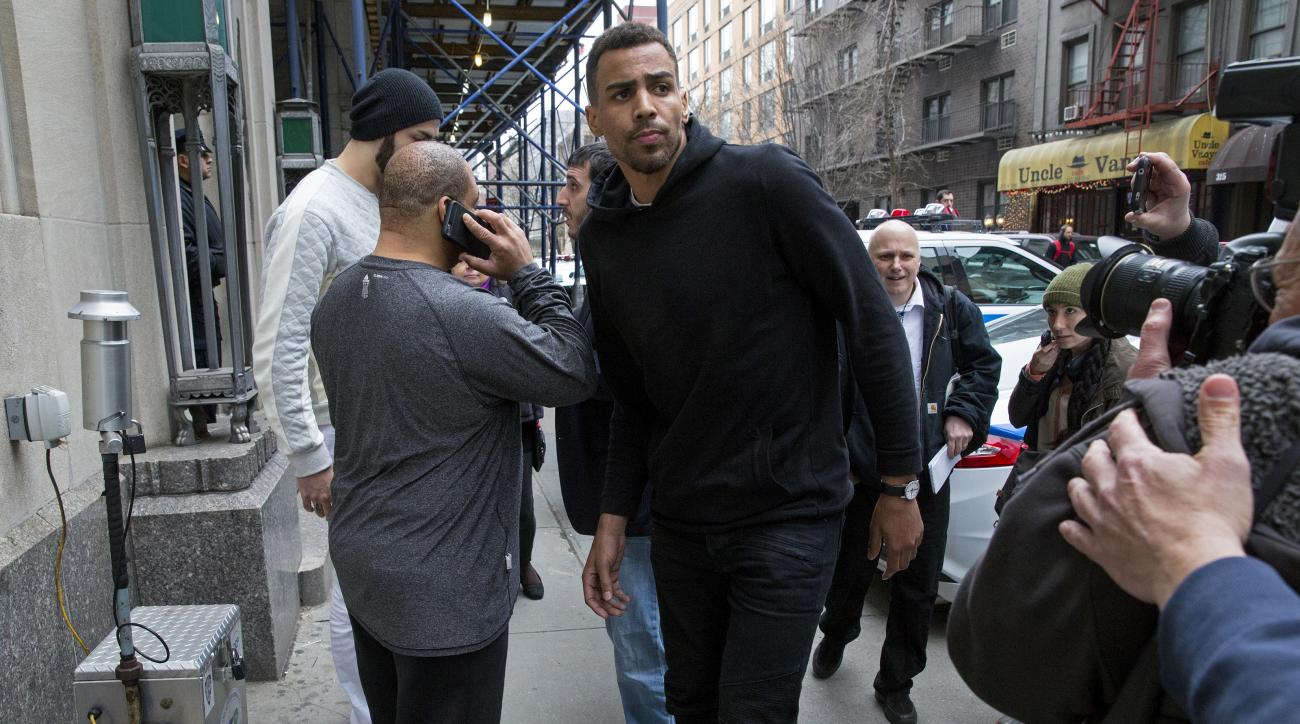 FILE - In this photo from Wednesday, April 8, 2015, Atlanta Hawks forward Thabo Sefolosha, center, leaves a courthouse in New York.  Sefolosha plans to fight charges he blocked officers from setting up a crime scene following the stabbing of Indiana Pacer