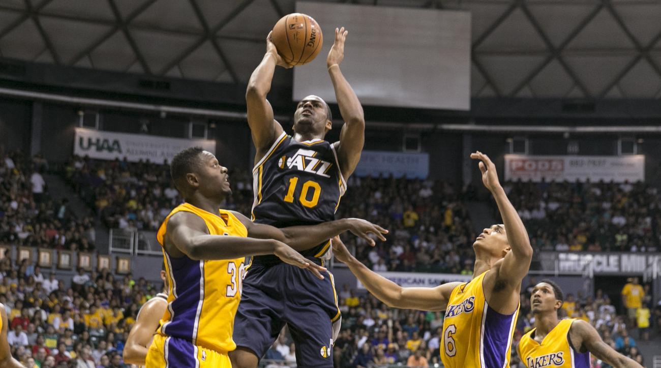 Utah Jazz guard Alec Burks (10) attempts a basket between Los Angeles Lakers forward Julius Randle (30), left, and Los Angeles Lakers guard Jordan Clarkson (6) during the second half of an NBA preseason basketball game, Tuesday, Oct. 6, 2015, in Honolulu.