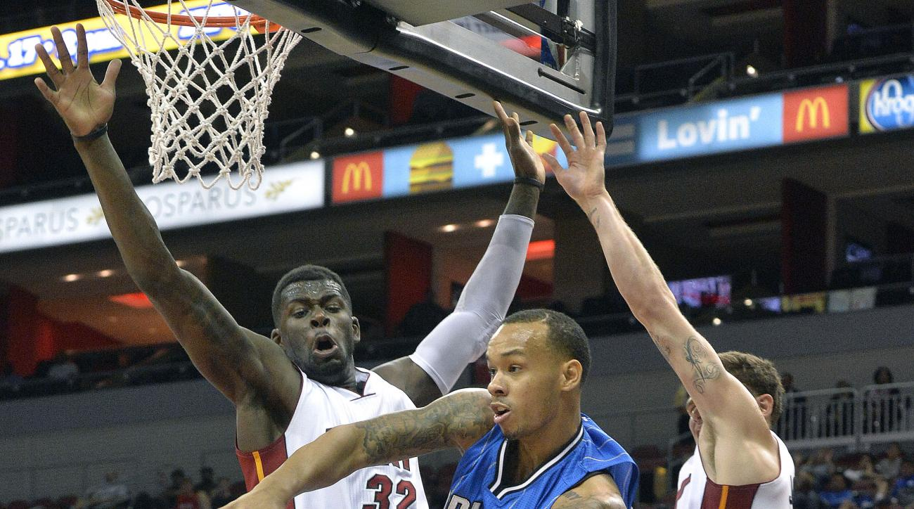 Orlando Magic's Shabazz Napier (13), passes around the defense of Miami Heat's C.J. Watson (32), during the second half of an NBA preseason basketball game, Wednesday, Oct. 7, 2015, in Louisville, Ky. Orlando defeated Miami 100-97. (AP Photo/Timothy D. Ea