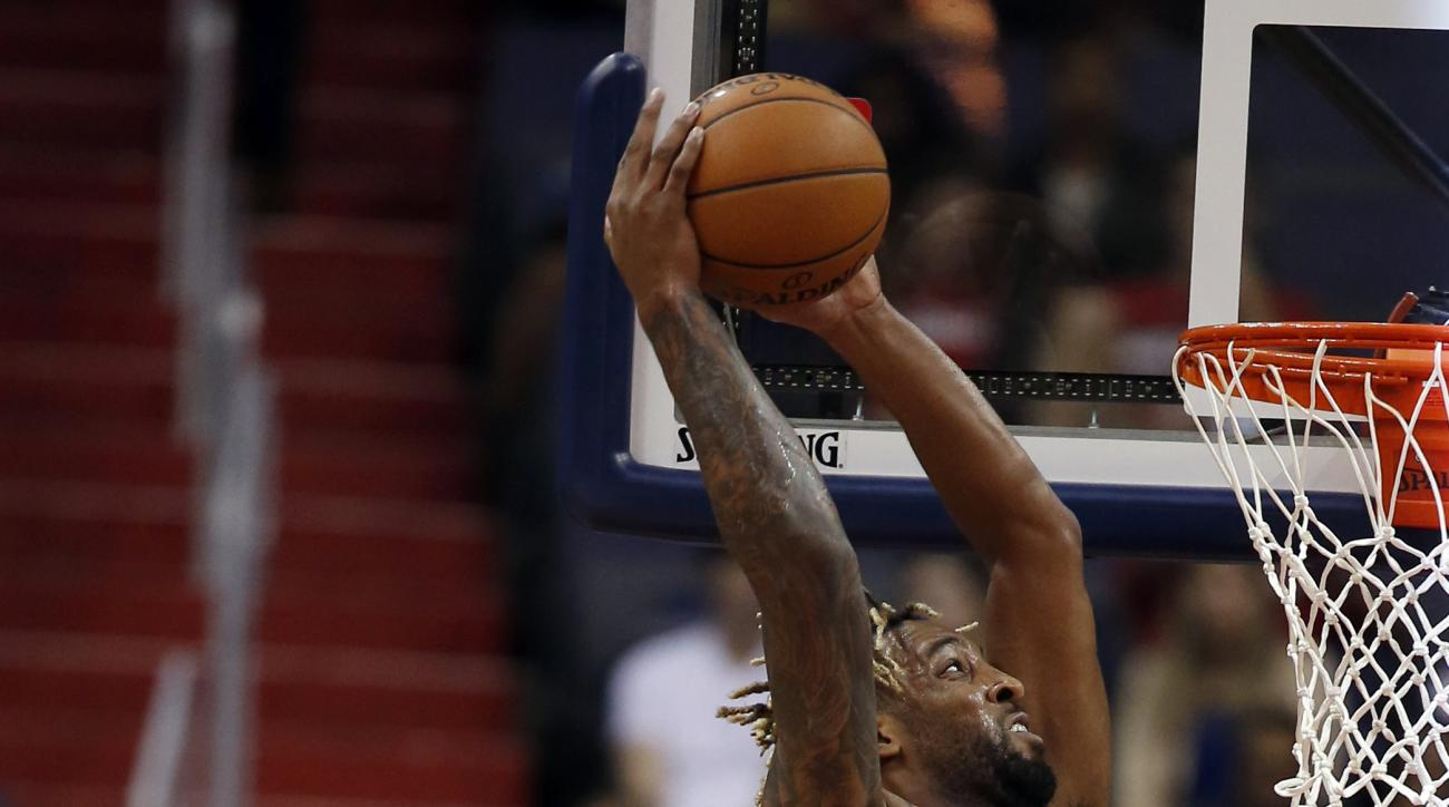 New York Knicks forward Derrick Williams (23) dunks over Washington Wizards forward Kelly Oubre Jr. (12) in the second half of an NBA preseason basketball game, Friday, Oct. 9, 2015, in Washington. The Knicks won 115-104. (AP Photo/Alex Brandon)