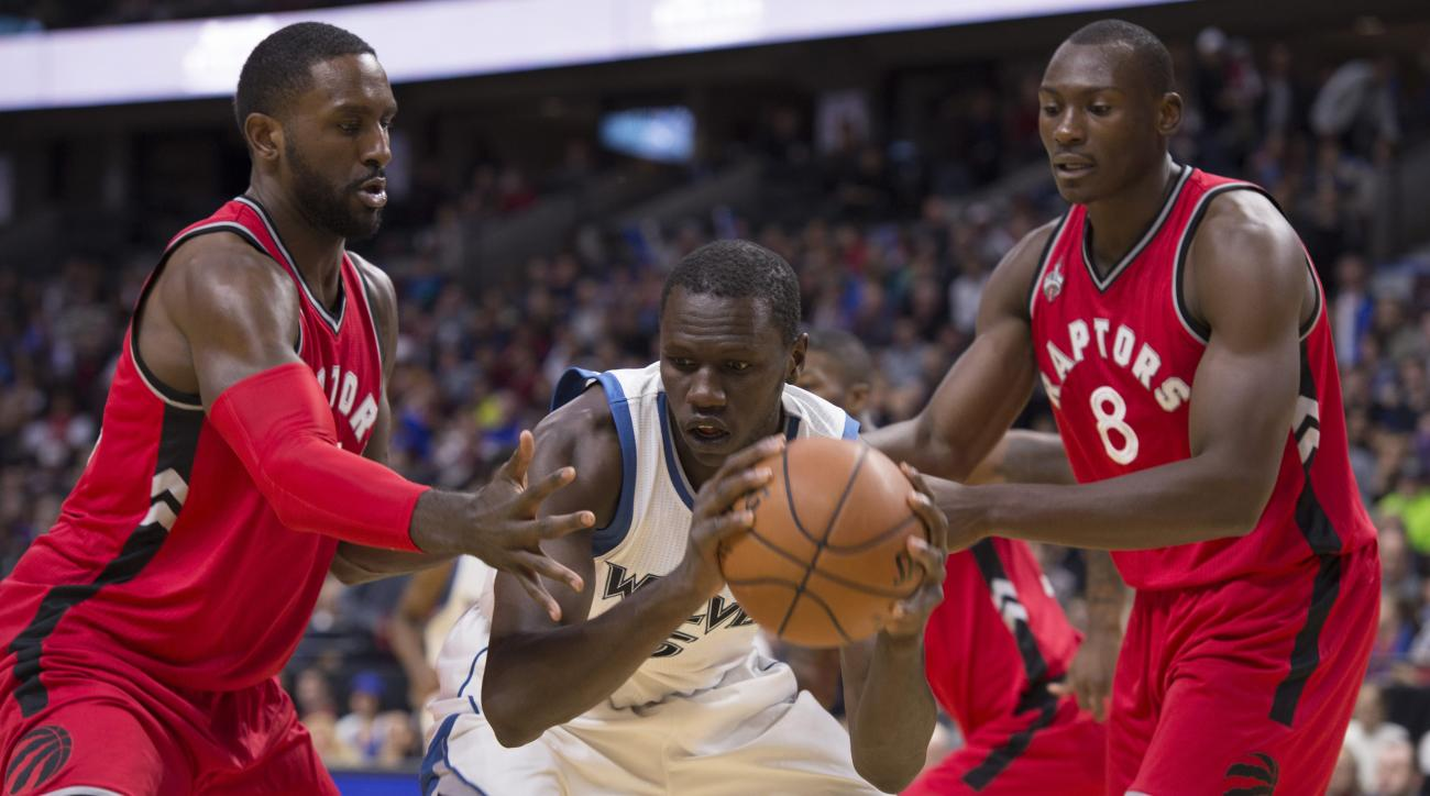 Minnesota Timberwolves center Gorgui Dieng, center, holds on to the ball under pressure from Toronto Raptors forwards Bismack Biyombo, right, and Patrick Patterson during first half  of an NBA preseason basketball game, Wednesday, Oct. 14, 2015 in Ottawa.
