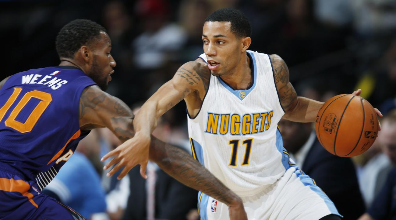 Denver Nuggets guard Erick Green, right, works the ball inside to shoot as Phoenix Suns guard Sonny Weems covers in the first half of an NBA basketball game Friday, Oct. 16, 2015, in Denver. (AP Photo/David Zalubowski)