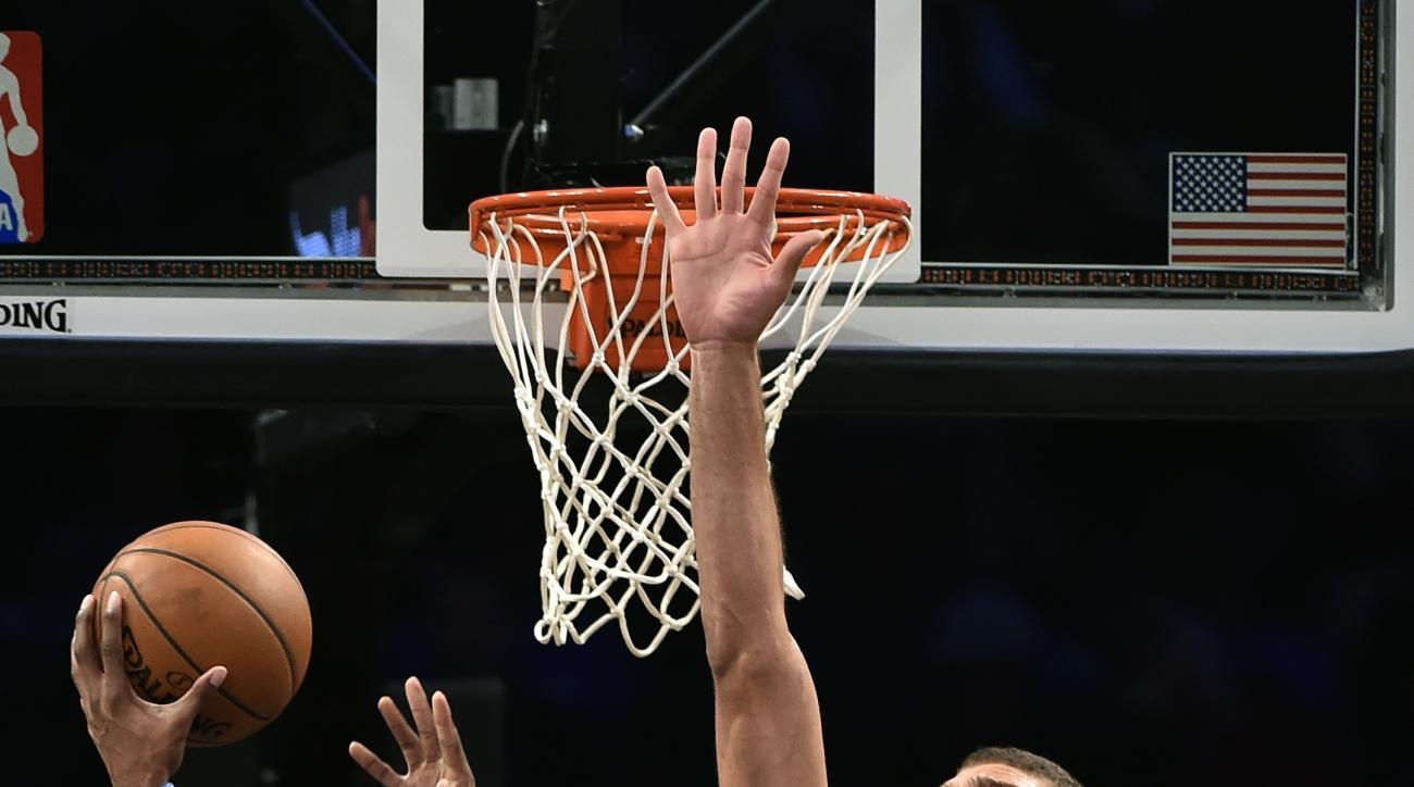 Brooklyn Nets center Brook Lopez (11) blocks Philadelphia 76ers forward Robert Covington's (33) shot at the basket during the second half of an NBA preseason basketball game on Sunday, Oct. 18, 2015, in New York. The Nets won 92-91. (AP Photo/Kathy Kmonic