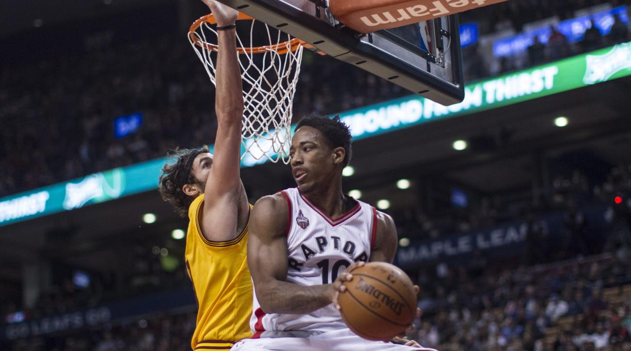 Toronto Raptors' DeMar DeRozan, right, plays a pass around Cleveland Cavaliers' Kevin Love during first-half preseason NBA basketball game action in Toronto, Sunday, Oct. 18, 2015. (Chris Young/The Canadian Press via AP) MANDATORY CREDIT