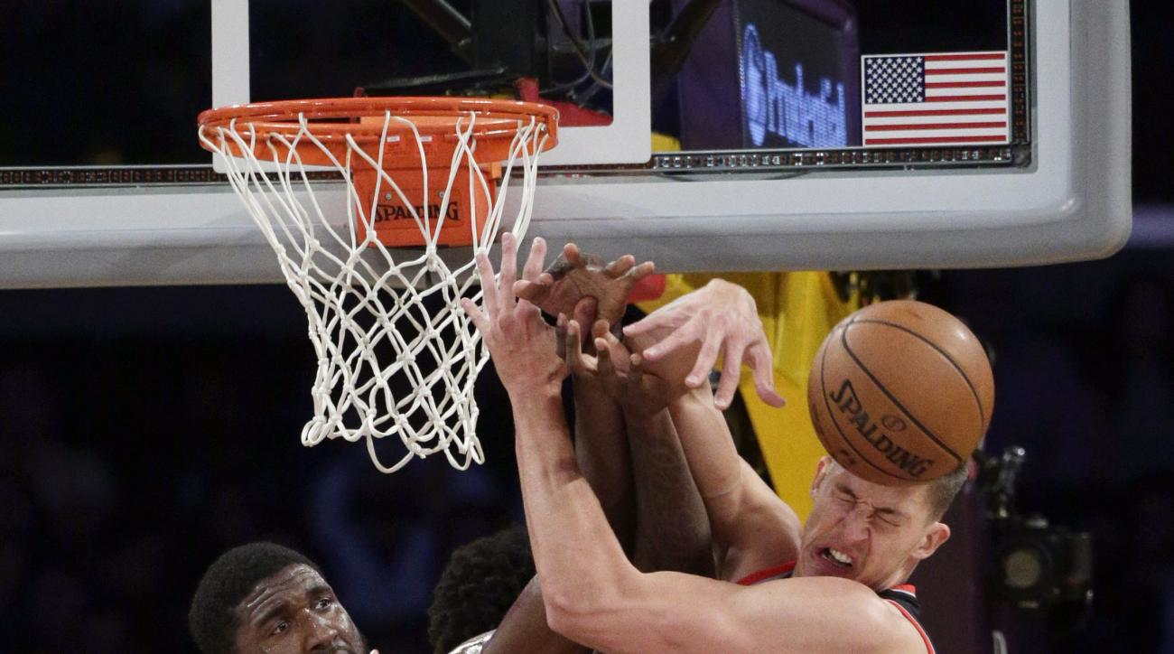 Los Angeles Lakers' Roy Hibbert, left, Portland Trail Blazers' Meyers Leonard fight for a rebound during the first half of an NBA preseason basketball game, Monday, Oct. 19, 2015, in Los Angeles. (AP Photo/Jae C. Hong)