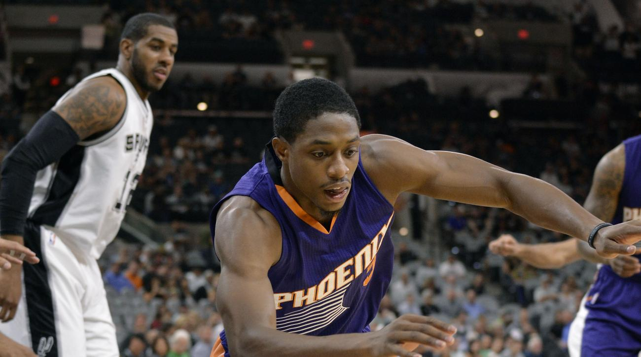 Phoenix Suns guard Brandon Knight chases the ball as San Antonio Spurs forward LaMarcus Aldridge, left, looks on during the first half of a preseason NBA basketball game, Tuesday, Oct. 20, 2015, in San Antonio. Phoenix won 104-84. (AP Photo/Darren Abate)