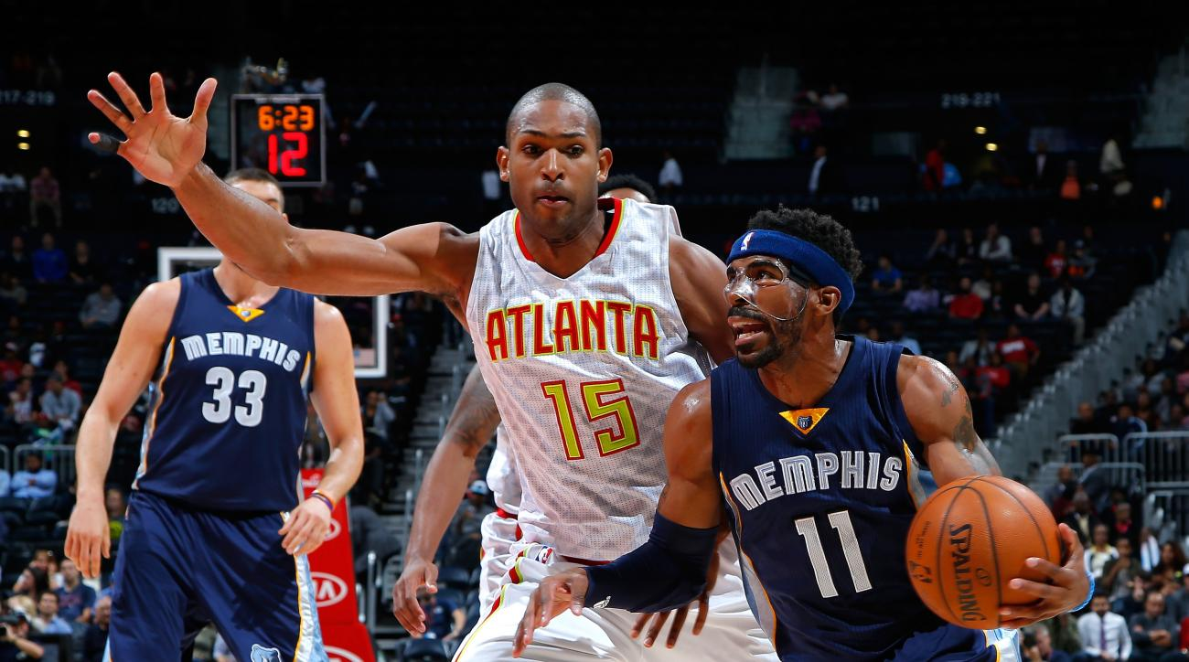 ATLANTA, GA - OCTOBER 21:  Mike Conley #11 of the Memphis Grizzlies drives against Al Horford #15 of the Atlanta Hawks at Philips Arena on October 21, 2015 in Atlanta, Georgia.  NOTE TO USER User expressly acknowledges and agrees that, by downloading ando