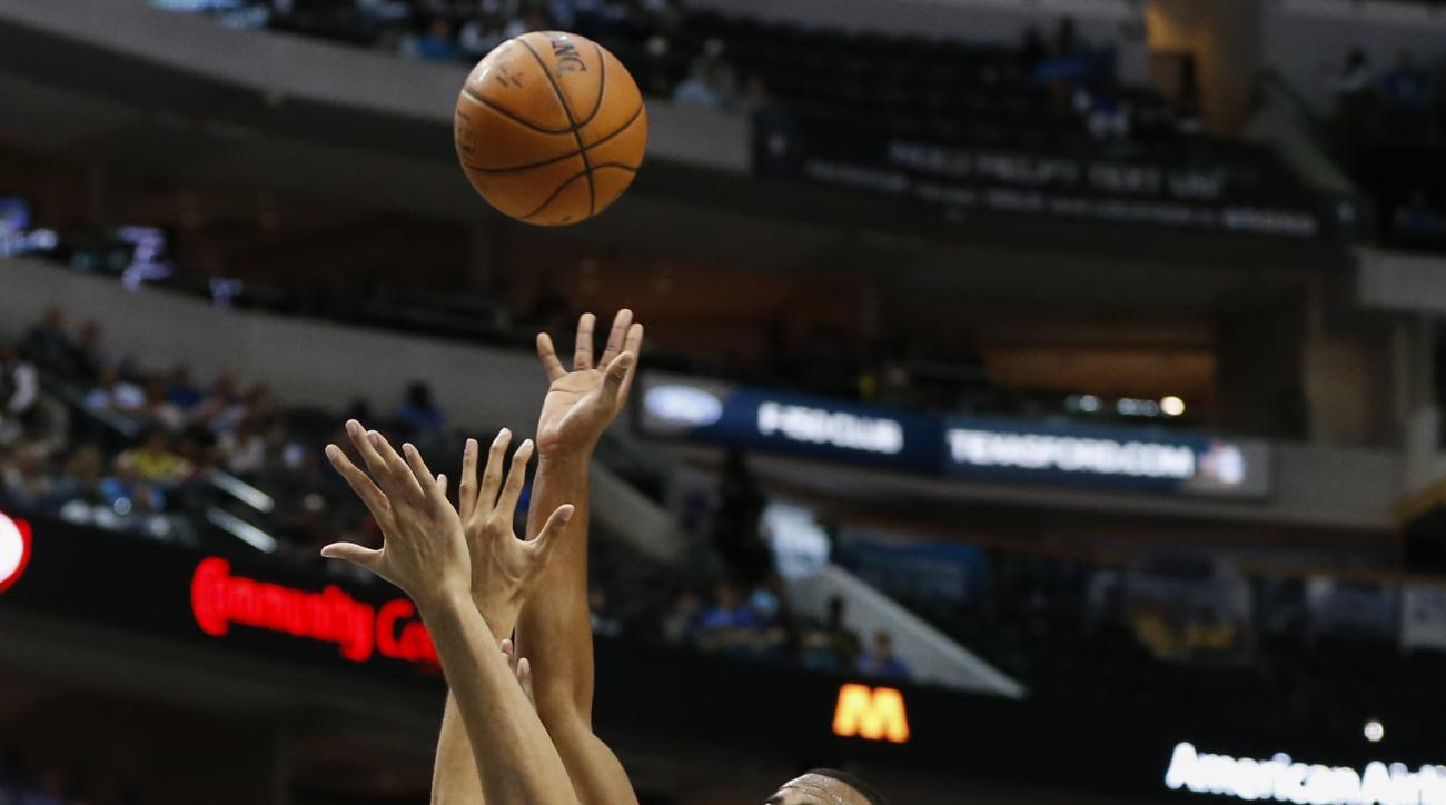 Phoenix Suns' T.J. Warren (12) shoots over Dallas Mavericks' Brandon Ashley (4) and Raymond Felton (2) during the first half of a preseason NBA basketball game, Wednesday, Oct. 21, 2015, in Dallas. (AP Photo/Jim Cowsert)