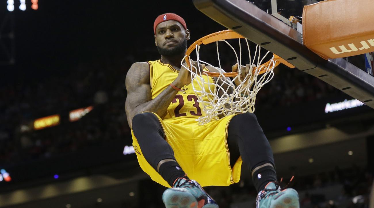 FILE - In this Dec. 25, 2014, file photo, Cleveland Cavaliers forward LeBron James (23) hangs onto the basket after a dunk during the second half of an NBA basketball game. More than any current player, LeBron James understands what it takes to reach the