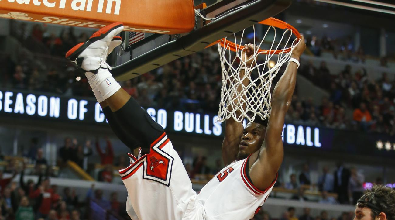 Chicago Bulls guard Jimmy Butler hangs on the rim after a dunk during the second half of an NBA basketball game against the Cleveland Cavaliers in Chicago, Tuesday, Oct. 27, 2015. The Bulls won the game 97-95. (AP Photo/Jeff Haynes)