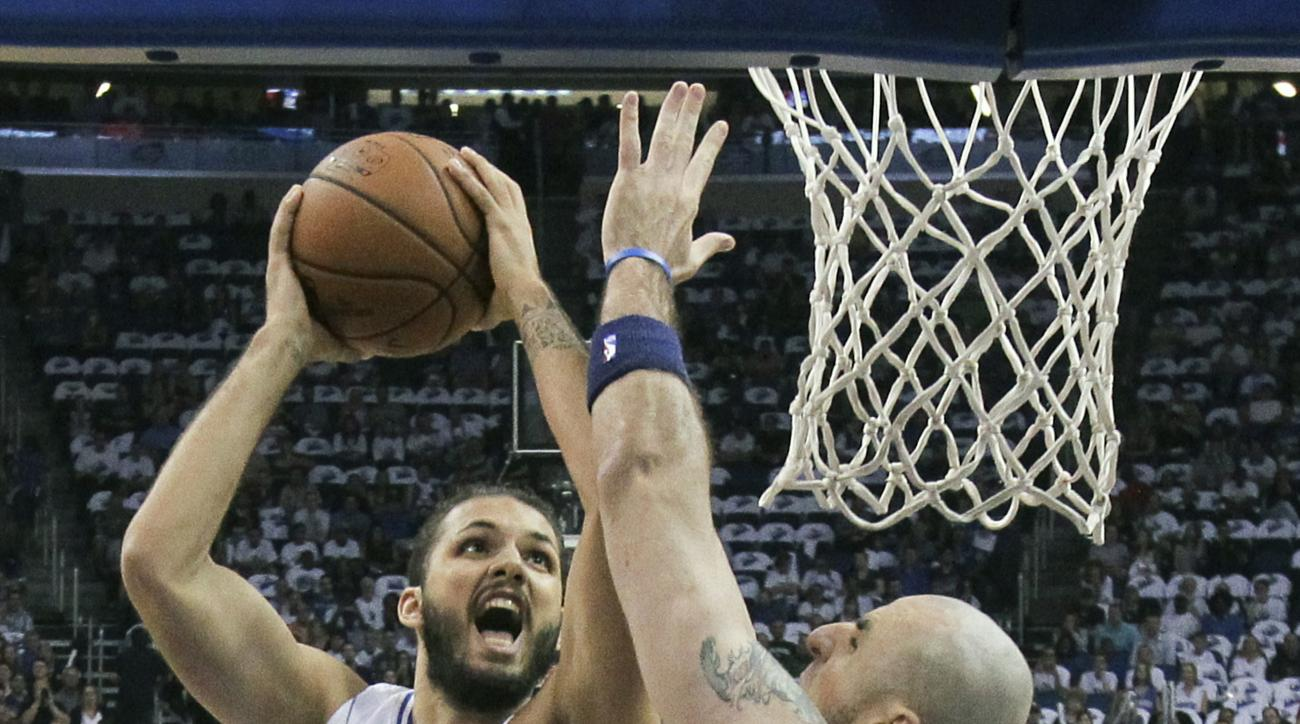 Orlando Magic guard Evan Fournier, left, goes up for a shot against Washington Wizards center Marcin Gortat, right, during the first half of an NBA basketball game, Wednesday, Oct. 28, 2015, in Orlando, Fla. (AP Photo/John Raoux)