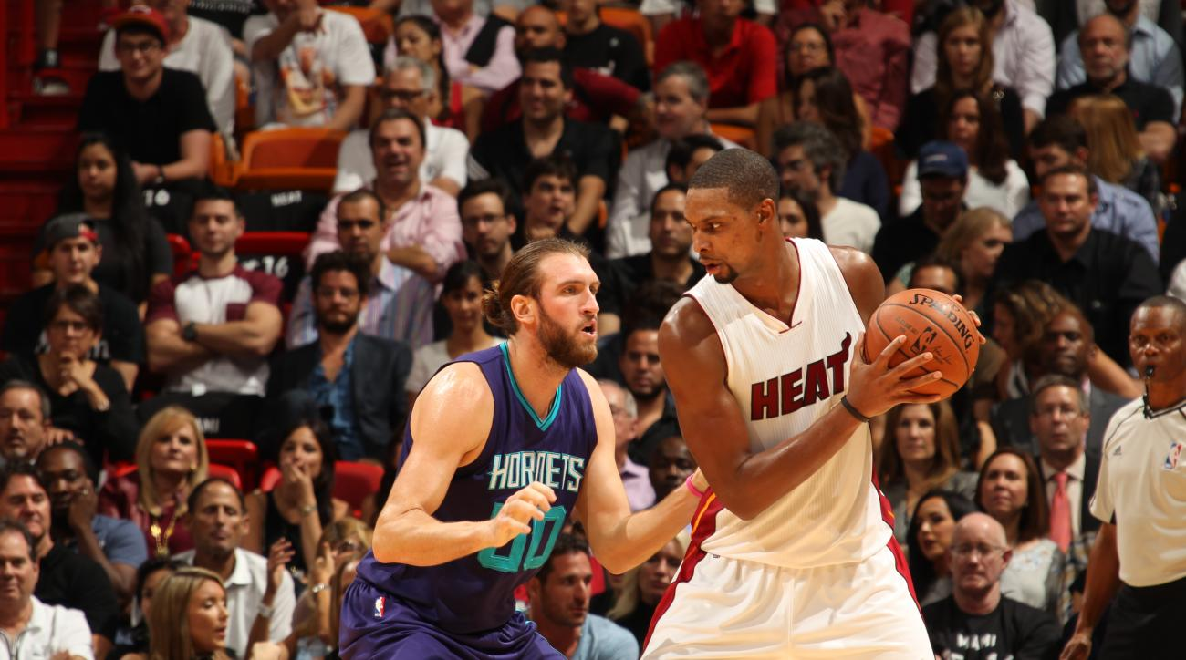 MIAMI, FL - OCTOBER 28:  Chris Bosh #1 of the Miami Heat handles the ball against Spencer Hawes #00 of the Charlotte Hornets on October 28, 2015 at AmericanAirlines Arena in Miami, Florida. (Photo by Issac Baldizon/NBAE via Getty Images)