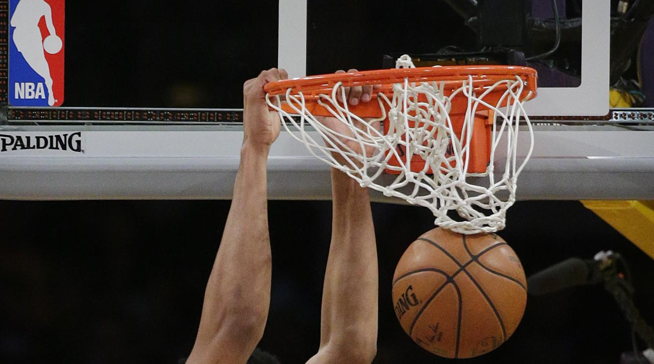 Minnesota Timberwolves' Karl-Anthony Towns, top, dunks during the first half of an NBA basketball game against the Los Angeles Lakers, Wednesday, Oct. 28, 2015, in Los Angeles. (AP Photo/Jae C. Hong)