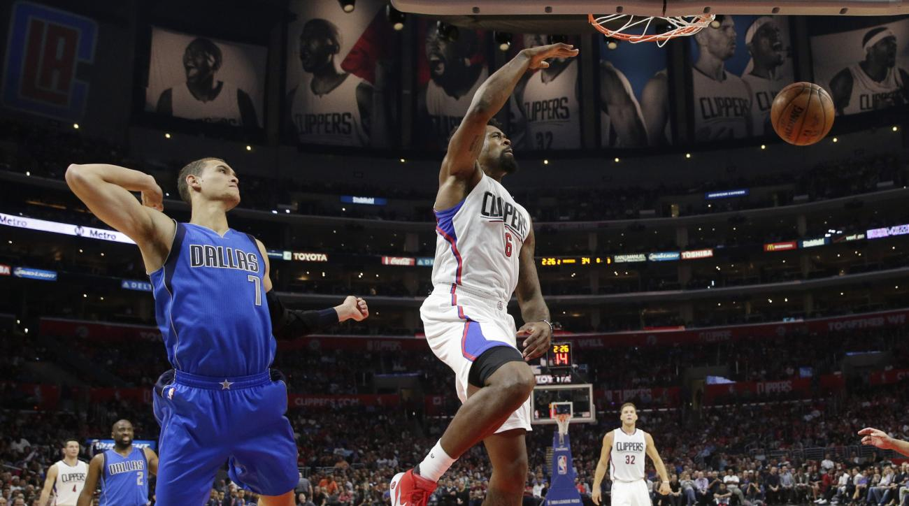 Los Angeles Clippers' DeAndre Jordan, center, dunks as Dallas Mavericks' Dwight Powell watches during the first half of an NBA basketball game, Thursday, Oct. 29, 2015, in Los Angeles. (AP Photo/Jae C. Hong)