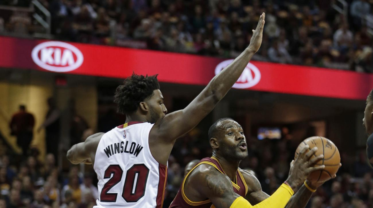 Cleveland Cavaliers' LeBron James, right, tries to get around Miami Heat's Justise Winslow in the first half of an NBA basketball game Friday, Oct. 30, 2015, in Cleveland. (AP Photo/Tony Dejak)