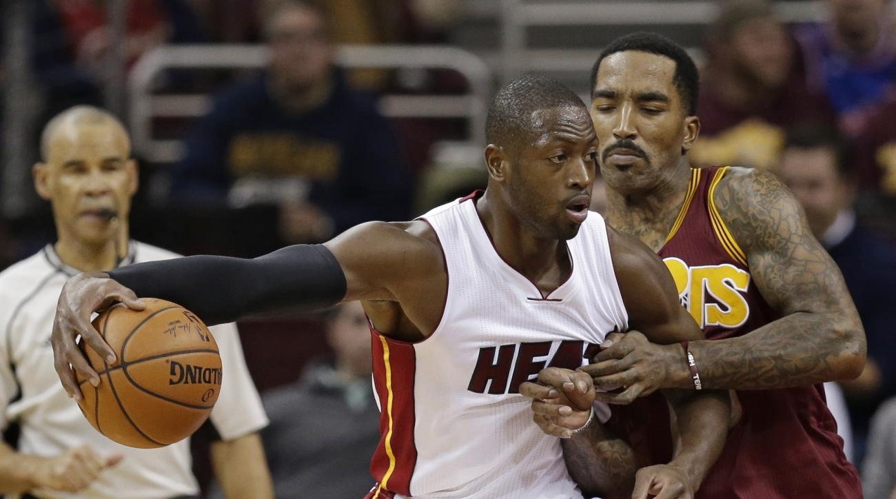 Miami Heat's Dwyane Wade, left, drives past Cleveland Cavaliers' J.R. Smith in the first half of an NBA basketball game Friday, Oct. 30, 2015, in Cleveland. (AP Photo/Tony Dejak)
