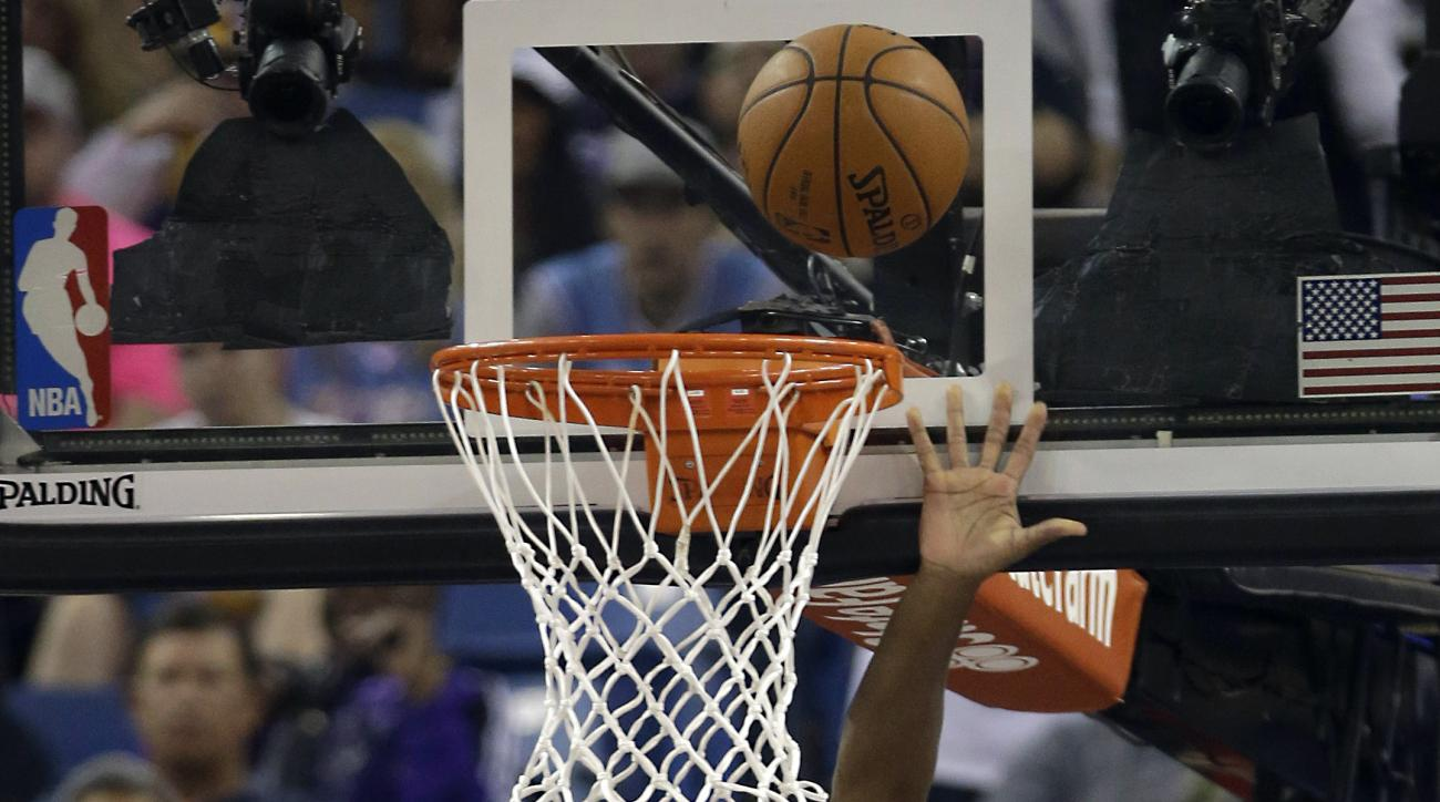 Sacramento Kings guard Rajon Rondo, center, goes for a layup as Los Angeles Lakers' Julius Randle, left, and D'Angelo Russell look on during the first quarter of an NBA basketball game in Sacramento, Calif., Friday, Oct. 30, 2015. (AP Photo/Rich Pedroncel