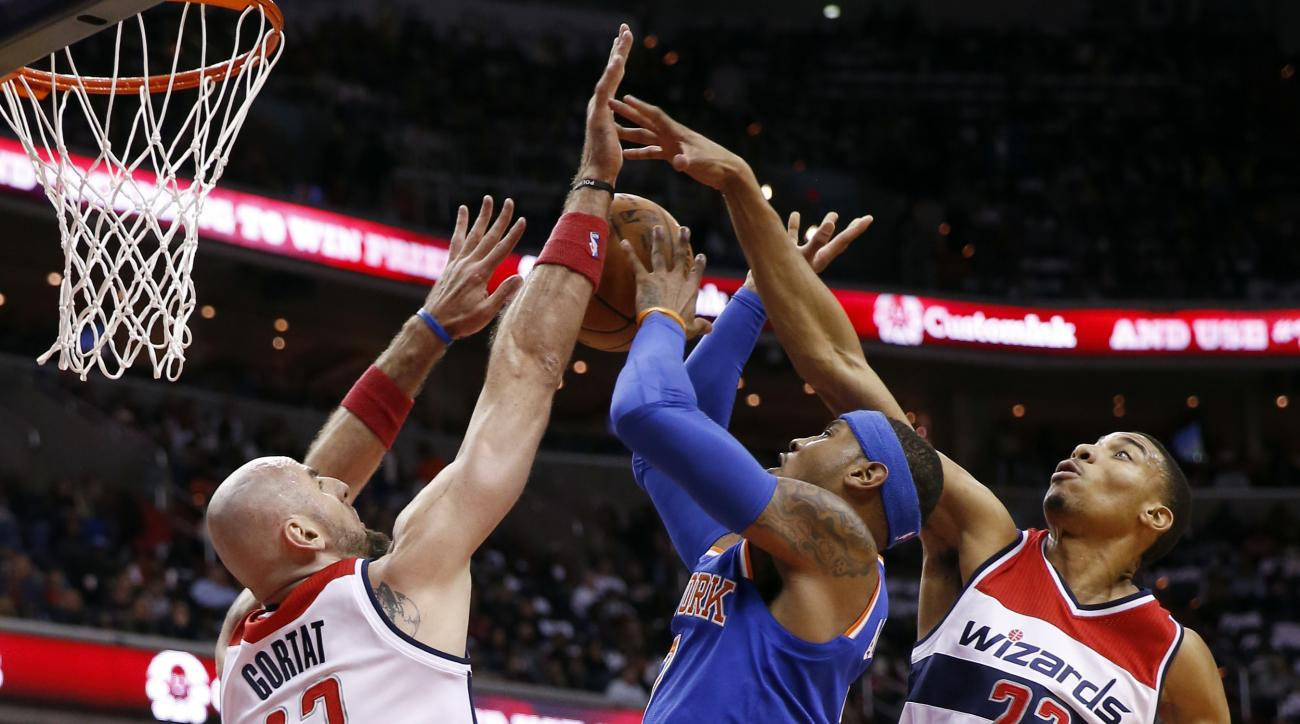 New York Knicks forward Carmelo Anthony, center,shoots between Washington Wizards center Marcin Gortat (13), from Poland, and forward Otto Porter Jr. (22) in the first half of an NBA basketball game, Saturday, Oct. 31, 2015, in Washington. (AP Photo/Alex