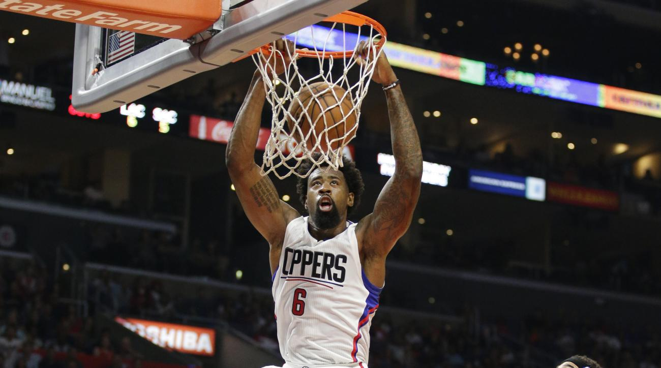 Los Angeles Clippers' DeAndre Jordan, center, dunks during the first half of an NBA basketball game against the Sacramento Kings, Saturday, Oct. 31, 2015, in Los Angeles. (AP Photo/Jae C. Hong)