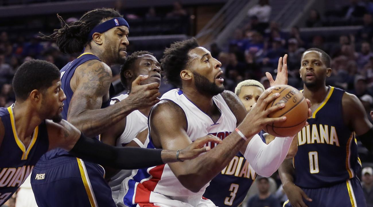 Detroit Pistons center Andre Drummond grabs a rebound while defended by Indiana Pacers forward Paul George, left, and center Jordan Hill, second from left, during the second half of an NBA basketball game, Tuesday, Nov. 3, 2015, in Auburn Hills, Mich. (AP