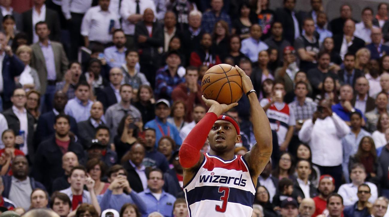 Washington Wizards guard Bradley Beal (3) goes up for the game-winning shot with coach Randy Wittman behind him, during the second half of an NBA basketball game against the San Antonio Spurs, Wednesday, Nov. 4, 2015, in Washington. The Wizards won 102-99