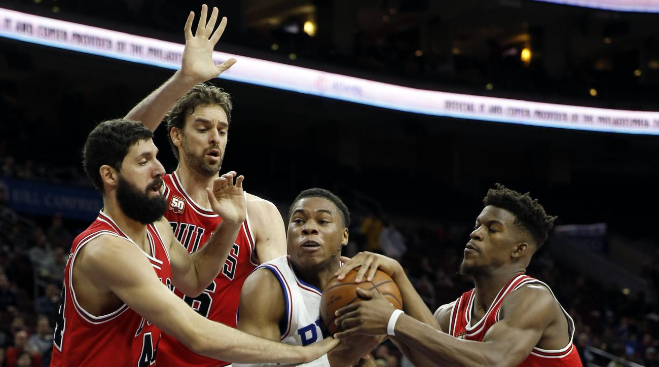 Philadelphia 76ers' Richaun Holmes, second from right, tries to hang onto the ball against Chicago Bulls' Jimmy Butler, from right, Pau Gasol and Nikola Mirotic in the first half of an NBA basketball game, Monday, Nov. 9, 2015, in Philadelphia. (AP Photo/