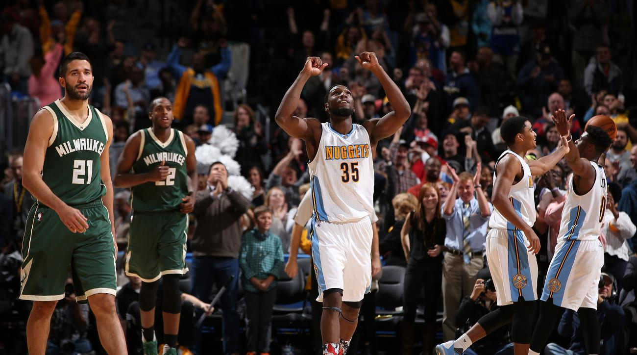 DENVER, CO - NOVEMBER 11:  Kenneth Faried #35 of the Denver Nuggets celebrates victory as Greivis Vasquez #21 and Khris Middleton #22 of the Milwaukee Bucks walk off the court at Pepsi Center on November 11, 2015 in Denver, Colorado. The Nuggets defeated