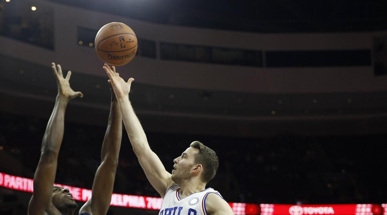 Philadelphia 76ers' Nik Stauskas (11) goes up for a shot between Indiana Pacers' Ian Mahinmi (28) and Paul George (13) during the first half of an NBA basketball game, Wednesday, Nov. 18, 2015, in Philadelphia. (AP Photo/Matt Slocum)