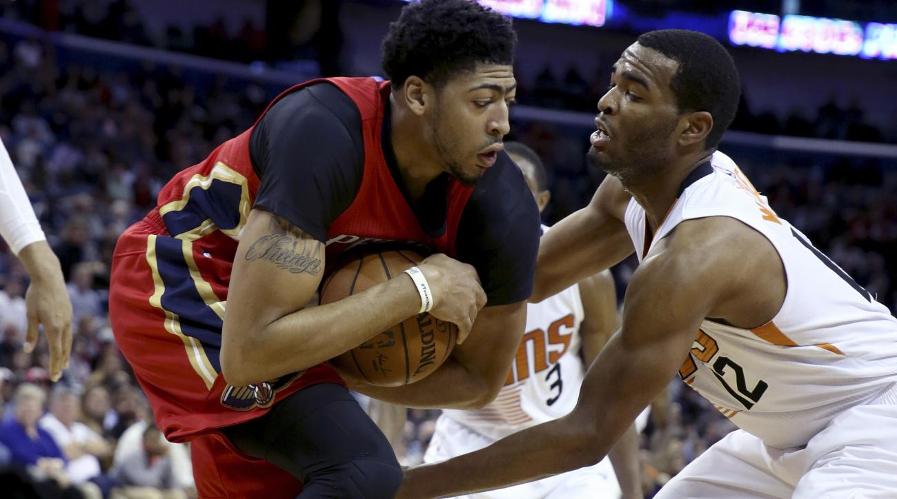 New Orleans Pelicans forward Anthony Davis, left, keeps a rebound away from Phoenix Suns forward T.J. Warren in the first half of an NBA basketball game in New Orleans, Sunday, Nov. 22, 2015. (AP Photo/Max Becherer)