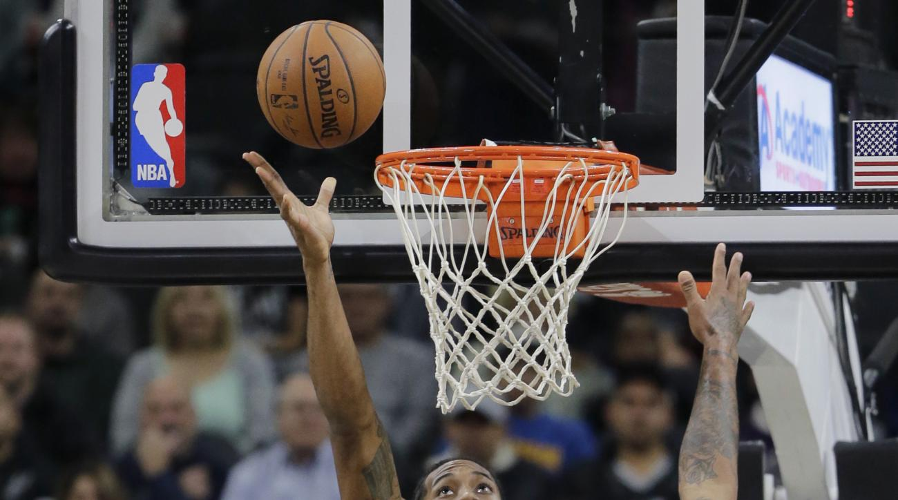 San Antonio Spurs' Kawhi Leonard (2) scores over Phoenix Suns defenders Tyson Chandler (4), Brandon Knight (3) and P.J. Tucker (17) during the first half of an NBA basketball game, Monday, Nov. 23, 2015, in San Antonio. (AP Photo/Eric Gay)