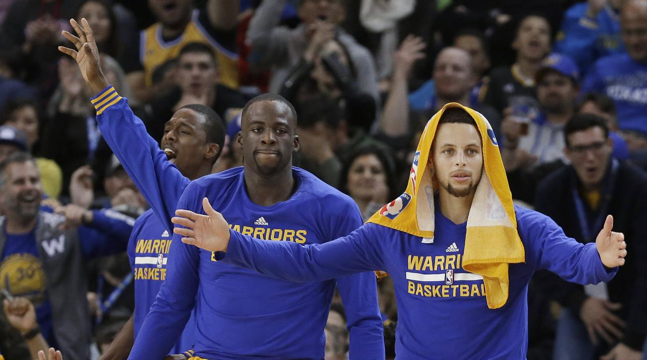 Golden State Warriors guard Stephen Curry, right, celebrates on the bench with forward Draymond Green, center, and forward Harrison Barnes during the second half of an NBA basketball game against the Los Angeles Lakers in Oakland, Calif., Tuesday, Nov. 24