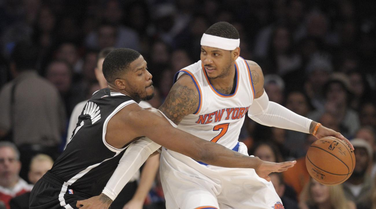 New York Knicks forward Carmelo Anthony, right, protects the ball as Brooklyn Nets forward Joe Johnson reaches in during the second quarter of an NBA basketball game Friday, Dec. 4, 2015, at Madison Square Garden in New York. (AP Photo/Bill Kostroun)
