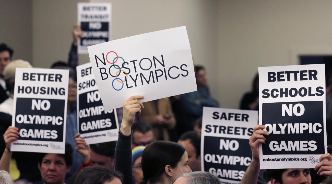 """FILE - In this Feb. 5, 2015, file photo, people hold up placards against the Olympic Games coming to Boston, during the first public forum regarding the city's 2024 Olympic bid, in Boston. Activists from """"No Boston Olympics"""" stirred up so much spirited op"""