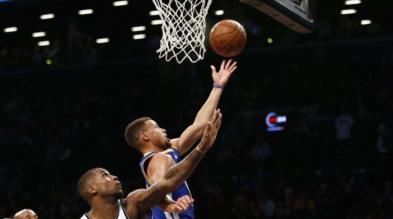 Golden State Warriors guard Stephen Curry (30) goes for a layup with Brooklyn Nets forward Thomas Robinson (41) defending in the first half of an NBA basketball game, Sunday, Dec. 6, 2015, in New York. (AP Photo/Kathy Willens)