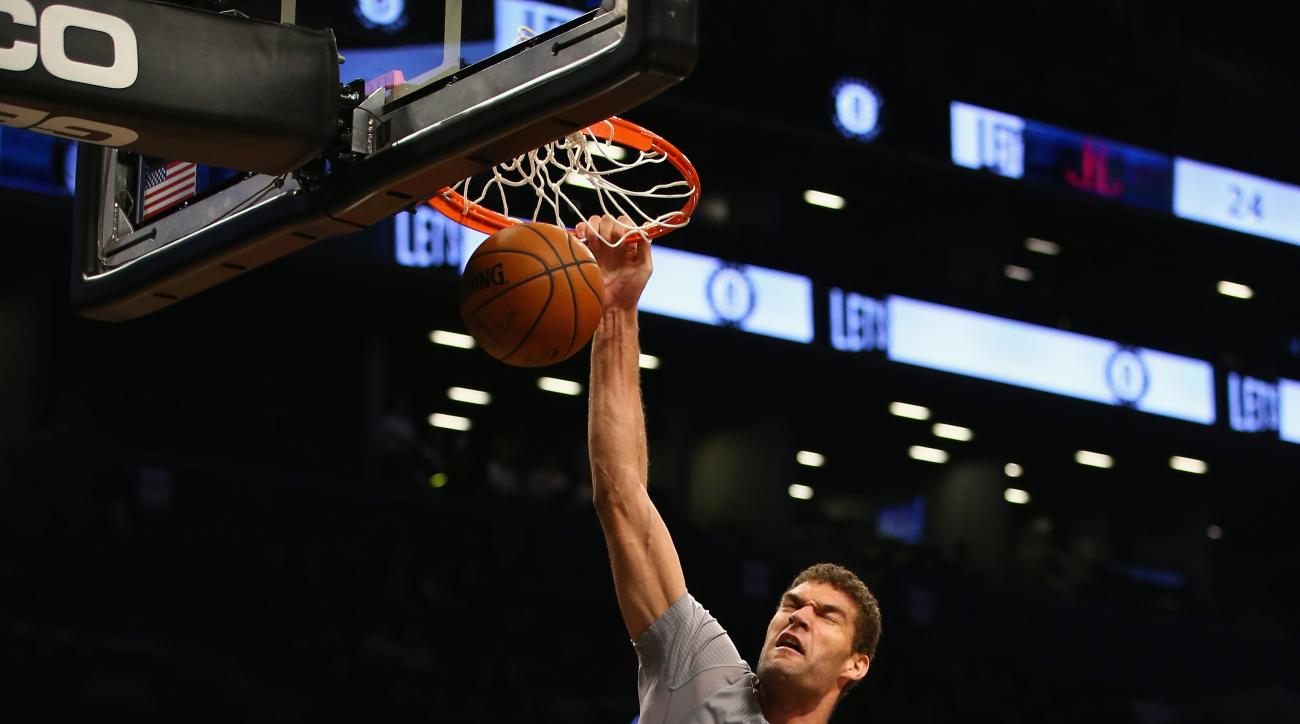 NEW YORK, NY - DECEMBER 08:  Brook Lopez #11 of the Brooklyn Nets dunks against Dwight Howard #12 and James Harden #13 of the Houston Rockets during their game at the Barclays Center on December 8, 2015  in the Brooklyn borough of New York City.  (Photo b