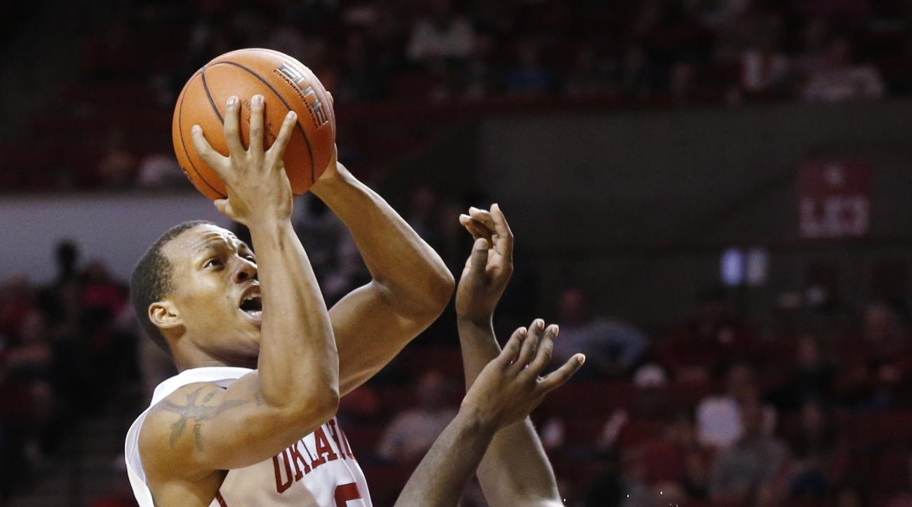 Oklahoma guard Dinjiyl Walker (2) is fouled by Oral Roberts guard Obi Emegano, right, as he shoots in the second half of an NCAA college basketball game in Norman, Okla., Saturday, Dec. 12, 2015. Oklahoma won 96-73. (AP Photo/Sue Ogrocki)