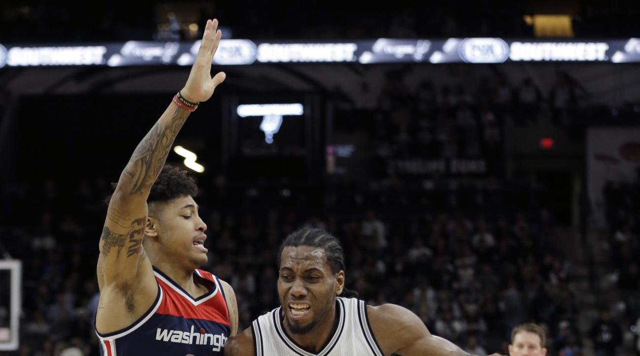 San Antonio Spurs forward Kawhi Leonard (2) drives around Washington Wizards forward Kelly Oubre Jr. (12) during the second half of an NBA basketball game, Wednesday, Dec. 16, 2015, in San Antonio. San Antonio won 114-95. (AP Photo/Eric Gay)