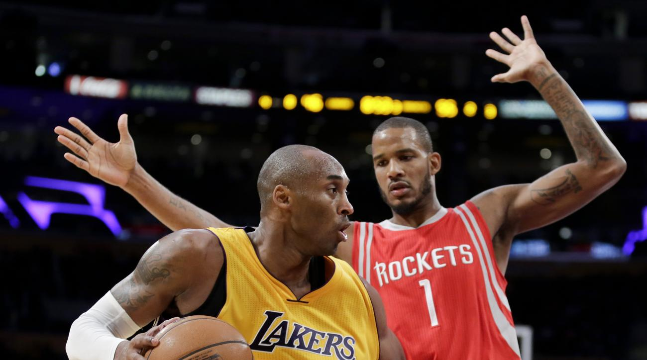 Los Angeles Lakers forward Kobe Bryant, left, drives around Houston Rockets forward Trevor Ariza during the second half of an NBA basketball game in Los Angeles, Thursday, Dec. 17, 2015. (AP Photo/Chris Carlson)