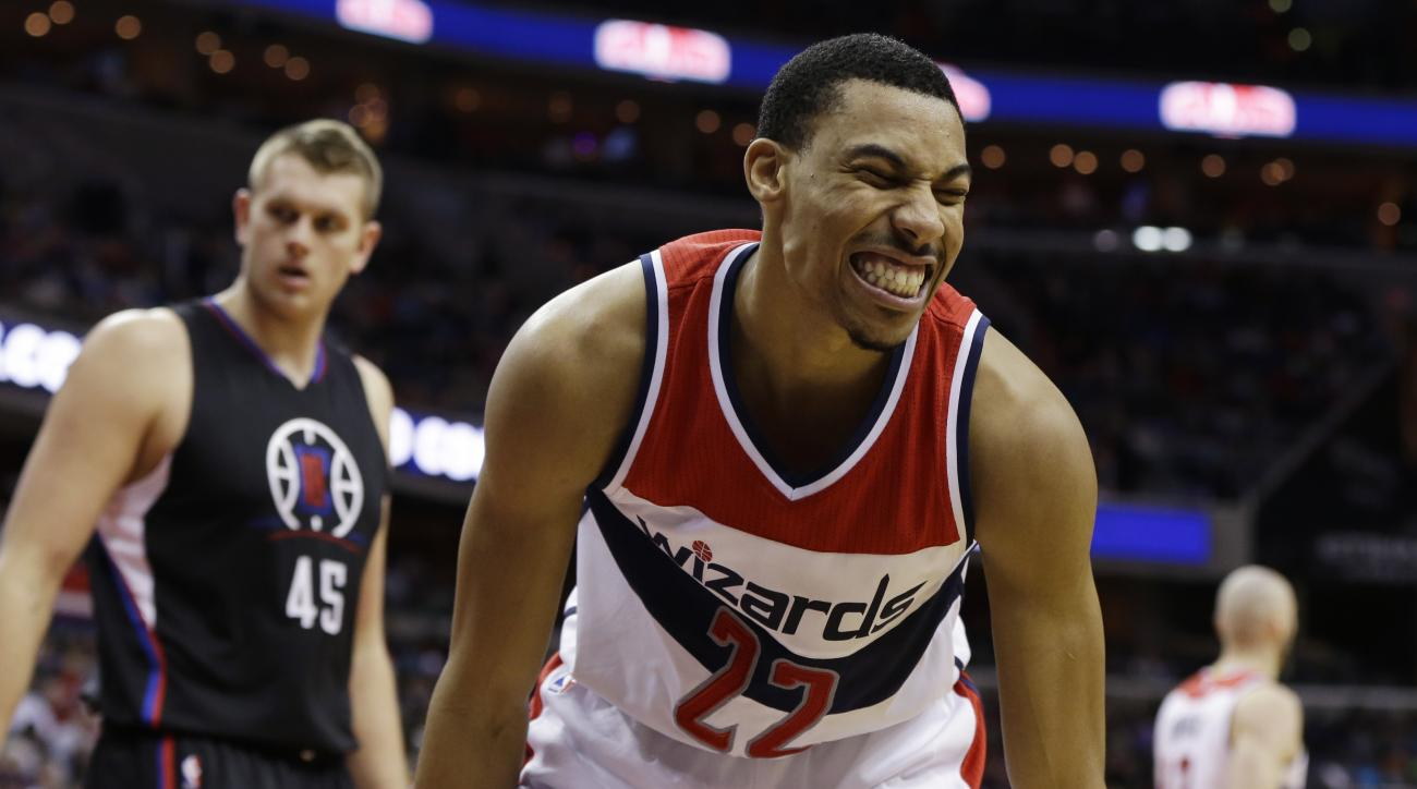 Washington Wizards forward Otto Porter Jr. (22) reacts to a call during the second half of the Wizards' NBA basketball game against the Los Angeles Clippers, Monday, Dec. 28, 2015, in Washington. in the background are Clippers center Cole Aldrich (45) and