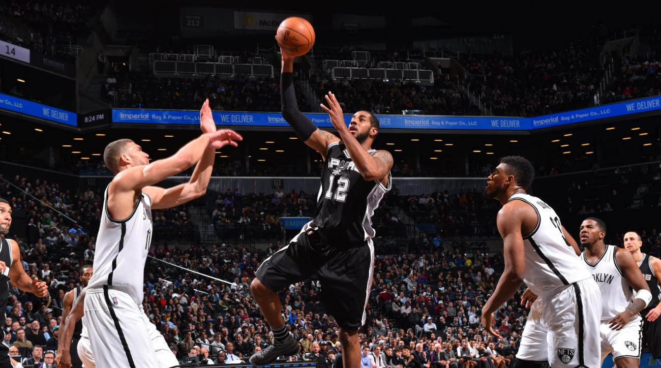 BROOKLYN, NY - JANUARY 11:  LaMarcus Aldridge #12 of the San Antonio Spurs goes up for the layup against the Brooklyn Nets on January 11, 2015 at Barclays Center in Brooklyn, New York. (Photo by Jesse D. Garrabrant/NBAE via Getty Images)