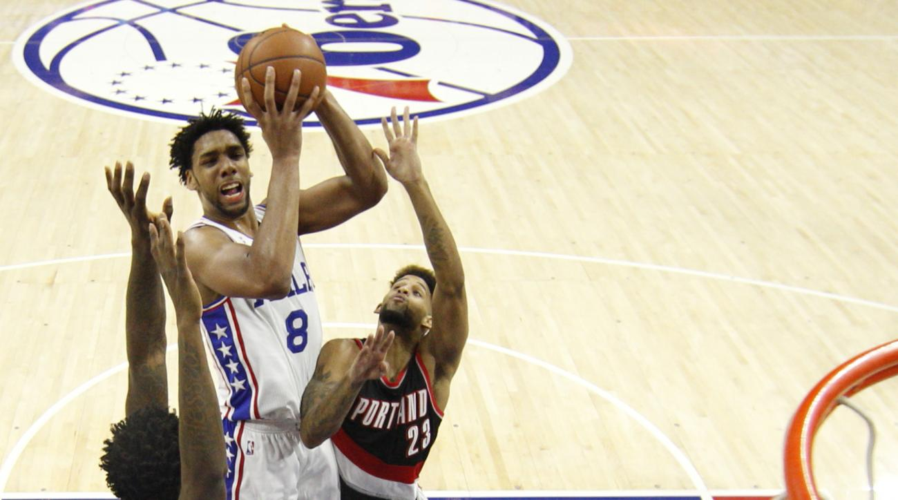 Philadelphia 76ers' Jahlil Okafor, center, goes up for the shot as he splits between Portland Trail Blazers' Ed Davis, left, and  Allen Crabbe, right, during the first half of an NBA basketball game, Saturday, Jan. 16, 2016, in Philadelphia. (AP Photo/Chr