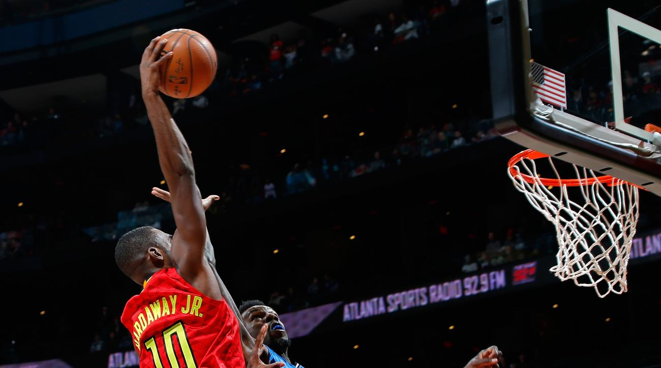 ATLANTA, GA - JANUARY 18:  Tim Hardaway Jr. #10 of the Atlanta Hawks dunks over Dewayne Dedmon #3 of the Orlando Magic at Philips Arena on January 18, 2016 in Atlanta, Georgia.  NOTE TO USER User expressly acknowledges and agrees that, by downloading and
