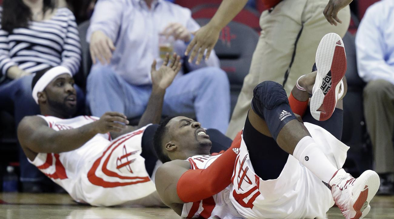 Houston Rockets' Dwight Howard, right, grimaces after a collision with teammate Ty Lawson in the first half of an NBA basketball game against the Detroit Pistons Wednesday, Jan. 20, 2016, in Houston. Howard limped off the court after the incident. (AP Pho