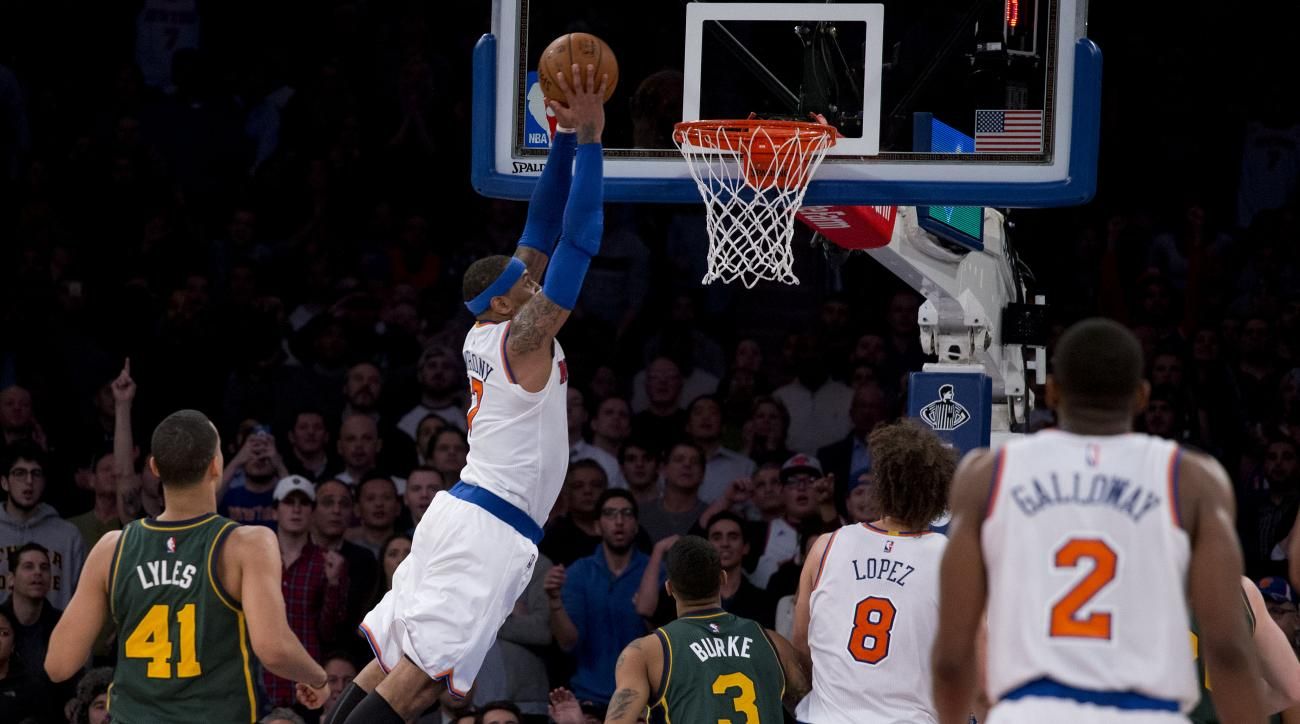 New York Knicks forward Carmelo Anthony (7) soars to the basket for a dunk against the Utah Jazz during the fourth quarter of an NBA basketball game, Wednesday, Jan. 20, 2016, in New York. The Knicks won 118-111 in overtime. (AP Photo/Julie Jacobson)
