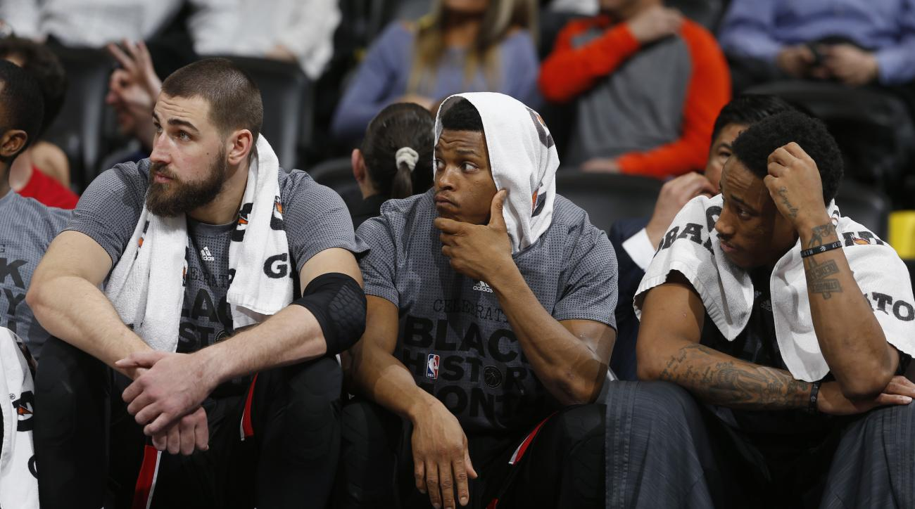 From left, Toronto Raptors center Jonas Valanciunas, of Lithuania, joins guards Kyle Lowry and DeMar DeRozan in looking on from the bench as time runs out in the second half of an NBA basketball game against the Denver Nuggets on Monday, Feb. 1, 2016, in