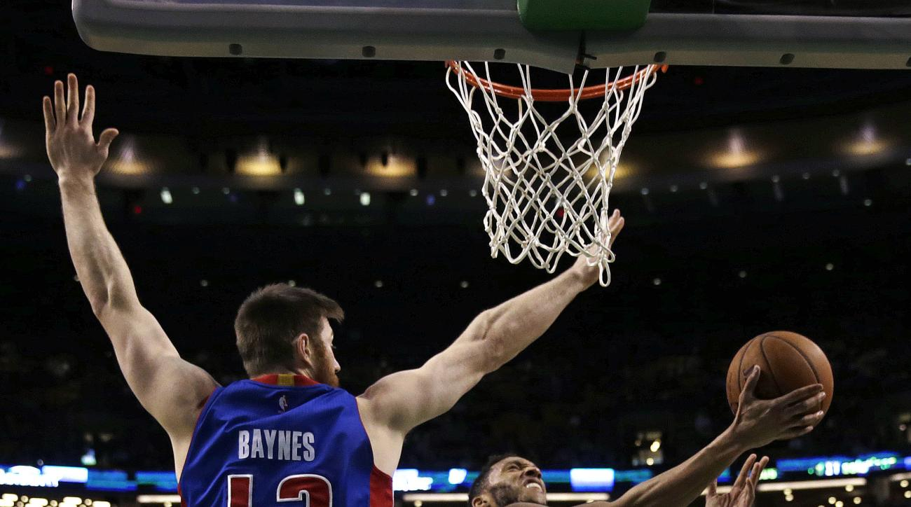 Boston Celtics guard Evan Turner (11) puts up a shot while covered by Detroit Pistons center Aron Baynes (12) during the second half of an NBA basketball game in Boston, Wednesday, Feb. 3, 2016. The Celtics defeated the Pistons 102-95. (AP Photo/Charles K