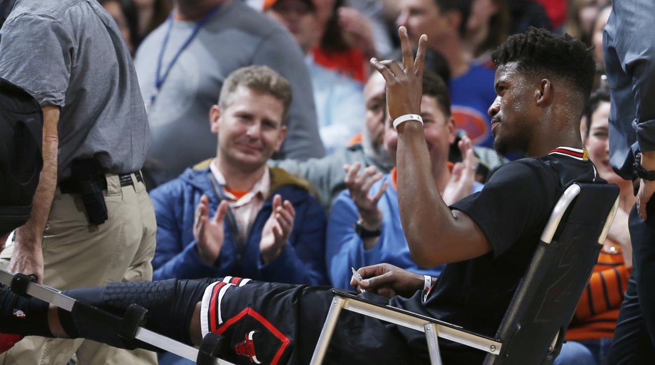 Chicago Bulls guard Jimmy Butler waves to fans as they applaud him while Butler is taken off the court after being injured late in the first half of his team's NBA basketball game against the Denver Nuggets on Friday, Feb. 5, 2016, in Denver. (AP Photo/Da
