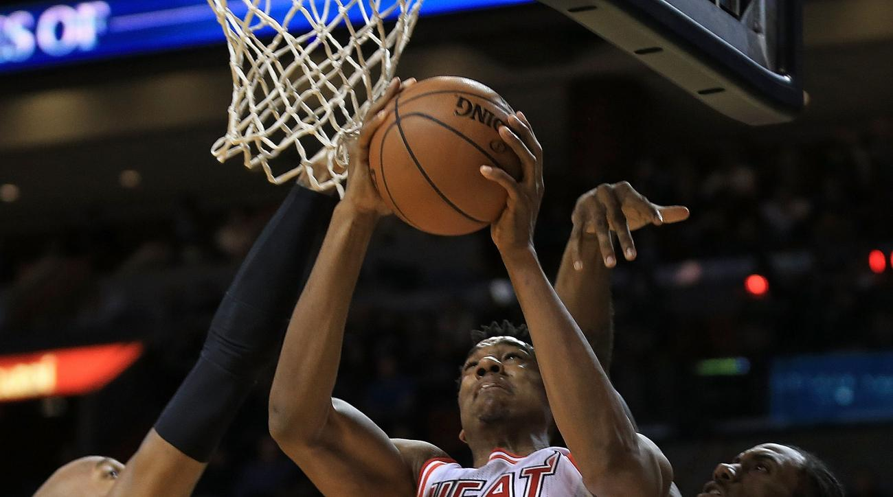 MIAMI, FL - FEBRUARY 09: Hassan Whiteside #21 of the Miami Heat goes up against David West #30 and Kawhi Leonard #2 of the San Antonio Spurs during a game  at American Airlines Arena on February 9, 2016 in Miami, Florida. (Photo by Mike Ehrmann/Getty Imag